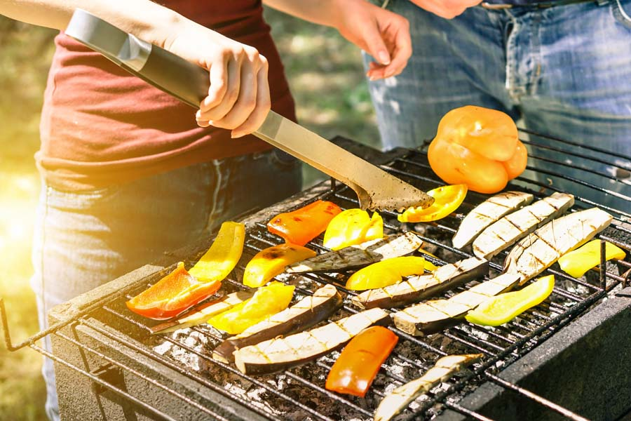 Young woman cooking vegetables for vegetarian barbecue dinner outdoor - Couple grilling peppers and aubergines for bbq - Vegan and healthy lifestyle concept - Soft focus on bottom barbecue tongs