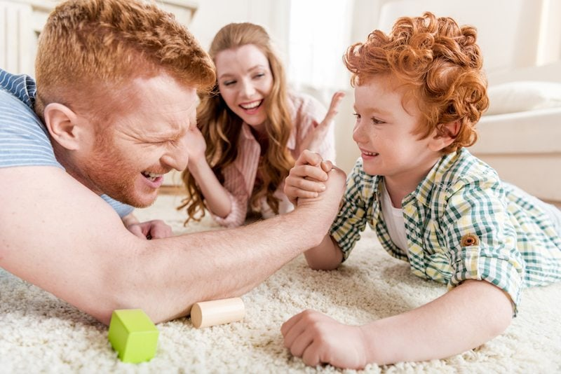Father and son playfully arm wrestle as mom looks on