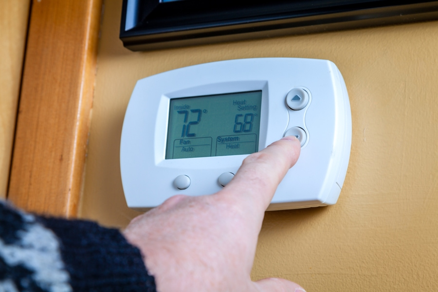Homeowner Adjusting Temperature On Their Thermostat