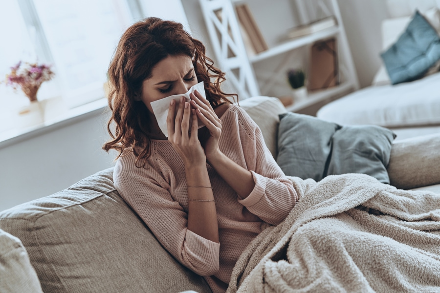Top view of sick young women blowing her nose using facial tissues while sitting on the sofa at home. How UV Lights Benefit Your HVAC System