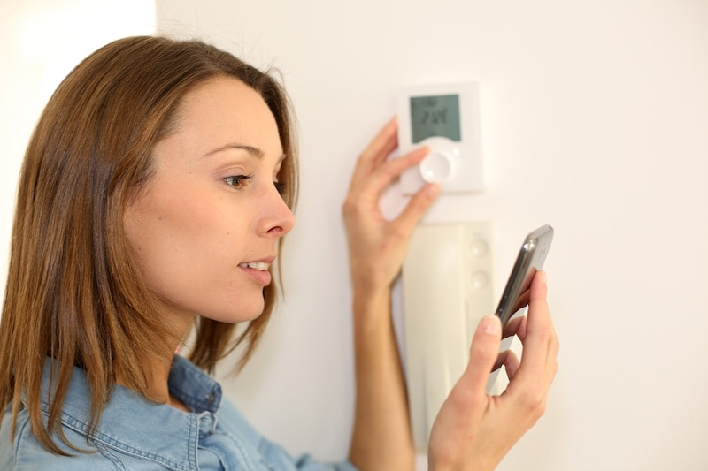 Woman regulating heater temperature on her programmable thermostat.