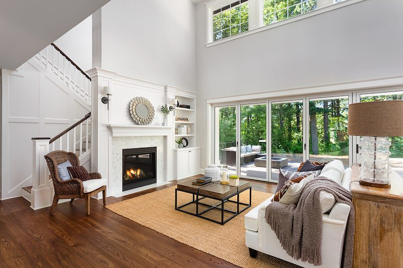 Beautiful living room interior with hardwood floors and fireplace in new luxury home with sliding glass doors and vaulted ceiling